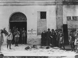 """15 giugno 1914 Circolo Monarchico in via Roma ad Alfonsine, dopo la devastazione.  A sinistra la Cavalleria Regia, a destra alcuni degli stessi dimostranti, in posa. La scritta """"W MASETTI"""" e """"ABBASSO L'ESERCITO"""" era lo slogan delle manifestazioni iniziali contro la guerra di Libia e contro l'esercito.  Masetti era un giovane muratore del bolognese, soldato di leva che, mentre stava partendo per la guerra di Libia, aveva sparato al suo colonnello inneggiando all'anarchia. Da un anno era chiuso in un manicomio criminale. Il palazzo fu acquistato poi da Tancredi Minarelli detto Plopi, anarchico, che lo adibì deposito del suo carro funebre e a stallatico. Ai piani superiori creò camere da affittare a gente povera. Giuseppe Marini poi acquistò da Plopi l'edificio, per usarlo come fabbrica per la produzione delle sue biciclette e poi delle moto """"Marini"""". Per questo oggi è detto """"Palazzo Marini"""". Donato dalla ditta MARINI spa-Fayat Group al Comune, è stata ristrutturata, e utilizzata come centro culturale."""